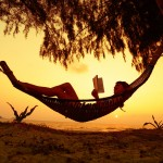 Young lady reading the book in the hammock on tropical beach at
